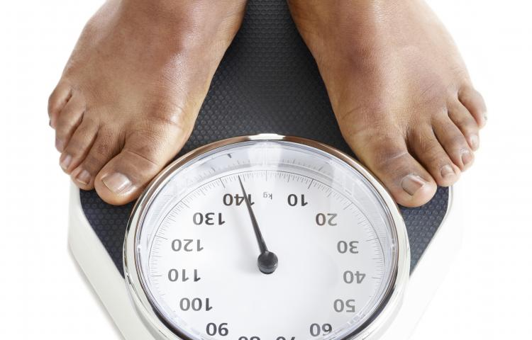 Man standing on weighing scales.
