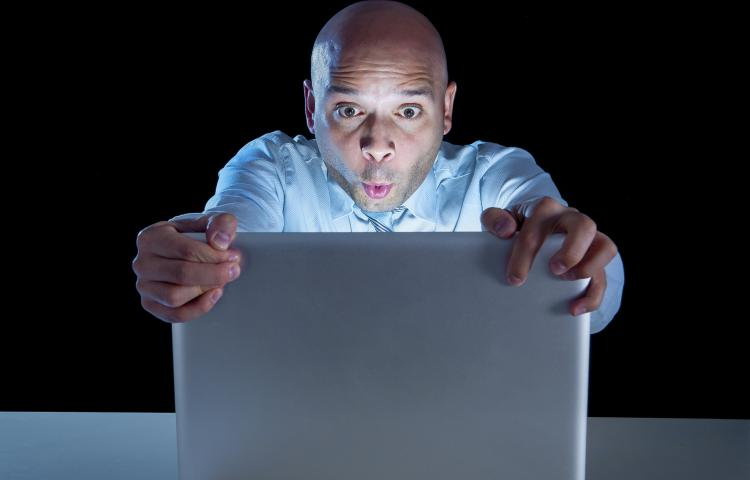 excited businessman alone at night sitting at computer laptop watching porn or online gambling isolated on black background on internet addiction concept