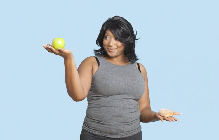 Mandatory Credit: Photo by Mood Board / Rex Features (2127523a) MODEL RELEASED Overweight mixed race woman holding green apple and donut over blue background VARIOUS
